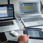 zarys postaci pracujacej nad digitalizacją przed nia na stole dwa laptopy i tablet