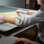 postac w rękawiczkach trzyma kartę manuskryptu nad stołem