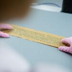 karta manuskryptu trzymana przez dłonie w różowych rękawiczkach