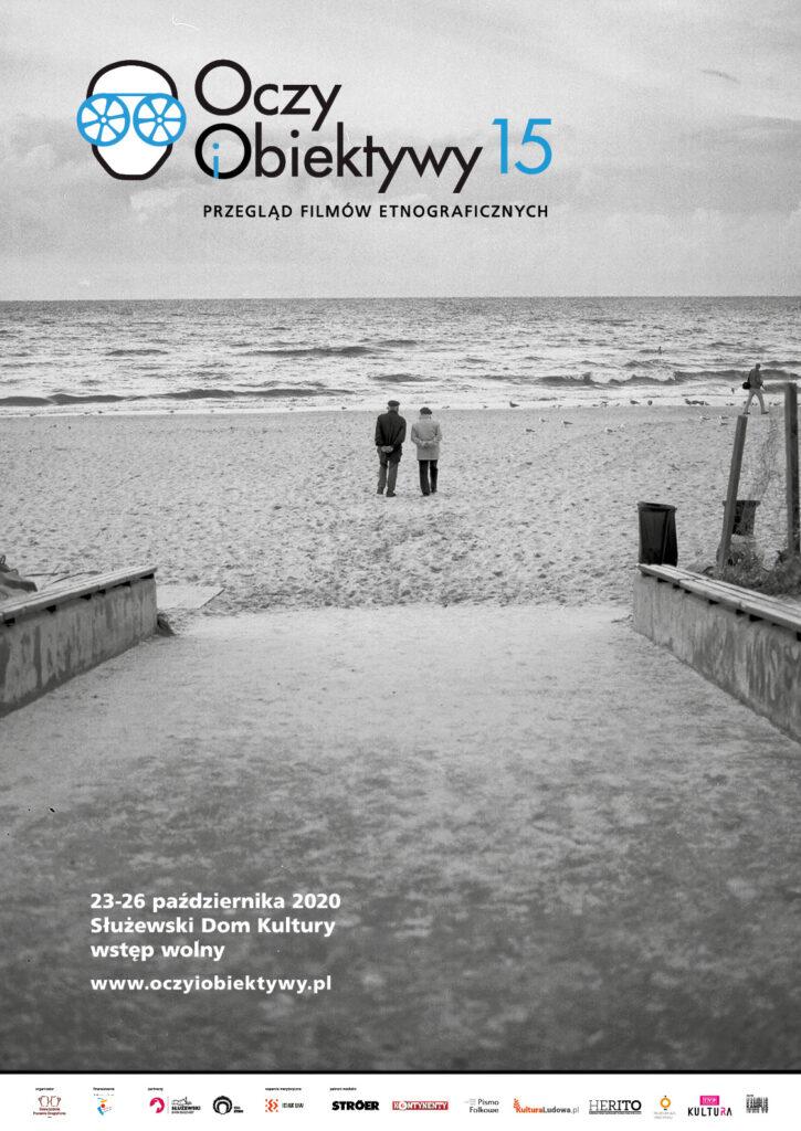 plakat na czarno-białym zdjeciu; 2 osoby na pustej plaży, w tle morze