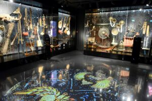Wnętrze części wystawy stałej. Pod ścianami w gablotach pod ścianami są różne instrumenty. Na podłodze wyświetlana kolorowa grafika.