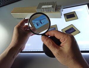 Na zdjęciu widoczne dłonie, jedna z nich trzyma lupę, druga pod lupą trzyma slajd. W tle na podświetlonym biurku leżą rozrzucone slajdy.
