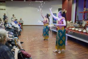 Po lewej stronie publiczność siedząca na krzesłach w rzędzie. Po prawej przed niewielką sceną dwie tancerki.