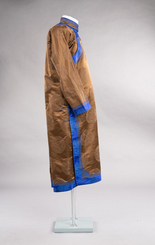 Mongolski płaszcz od boku, widoczny na szarym tle.