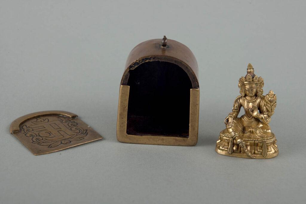 Otwarty przenośny relikwiarz, obok stoi mosiężny posążek.